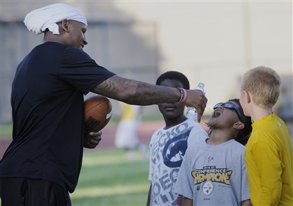 20140603jrSteelersLocal4-3 Steelers first-round draft pick Ryan Shazier helps Tyson Ronel, 10, of Allison Park with a drink of water Tuesday during a football clinic put on by the Steelers and Urban Impact Foundation at Oliver Citywide Academy.