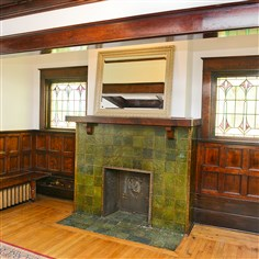 The den  The den features the original a fireplace with tile surround , stained glass windows and rich woodwork.