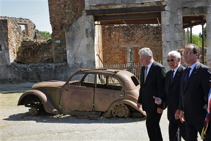 AP620408309471 French President Francois Hollande, right, German President Joachim Gauck, left, and Robert Hebras, 88, one of the last survivors of the World War II massacre in Oradour-sur-Glane, center, walk in the streets of the village in 2013.