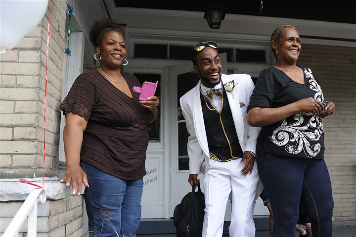 20140613Wilkinsburg2 James Herbert, 19, along with his aunt Cynthia Herbert, left, and mother June Howard, right, watch as the limo pulls up to his house in Wilkinsburg on prom night Thursday, May 29. Friends and family gathered at James' house to take photos of him.