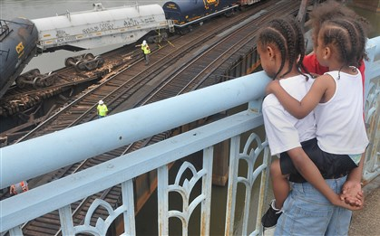20140608lrderailstandalone03-2 Children watch as railroad personnel survey a train that derailed late Saturday.