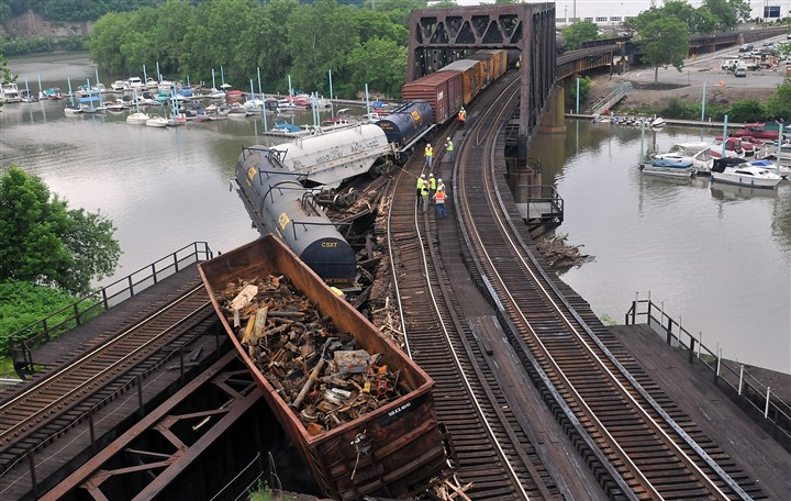 20140608lrderailstandalone01 Cars from a derailed train hang over the water of the McKeesport Marina.