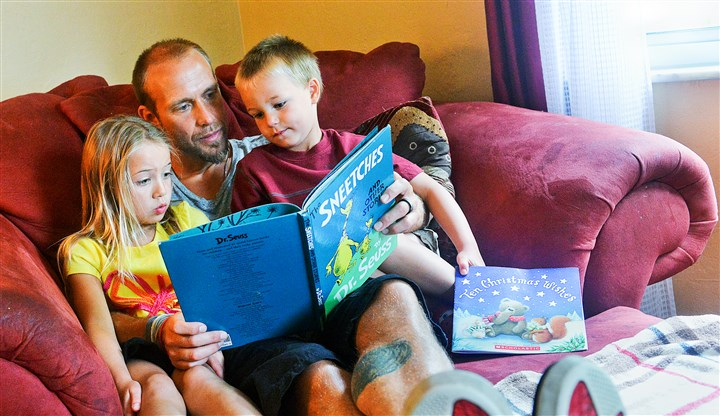 20140906lrstaydadmag06-3 Dakota Jablon, 3, and his sister Lyla, 6, settle into a super-sized chair in the living room with their father, Jason Jablon, to read some books.