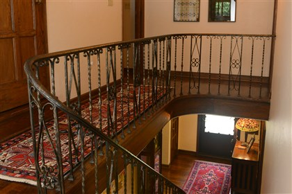 A beautiful, ornate metal railing A beautiful, ornate metal railing leads the front entryway to the second floor. The home features hardwood floors, leaded glass windows and five bedrooms.