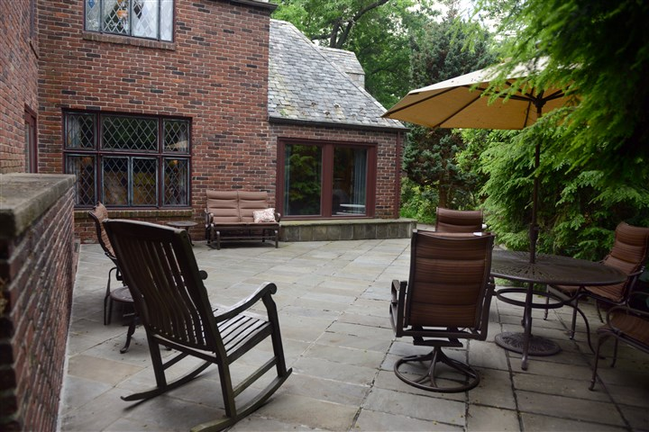 "A spacious stone patio  A spacious stone patio just off the kitchen in the English Cotswold-style stone ""cottage"" built in 1938 is a wonderful gathering place for family and friends. The patio also leads to a small grassy area in the yard."