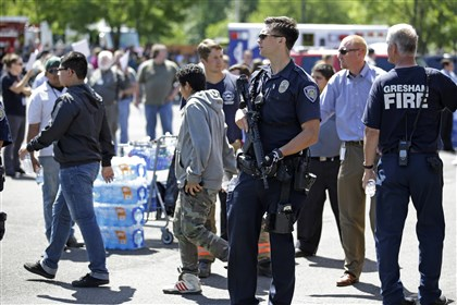 Oregon School Shooting A police officer stands guard as students arrived by bus at a shopping center parking lot in Wood Village, Ore., after a shooting at Reynolds High School Tuesday, June 10, 2014, in nearby Troutdale. A gunman killed a student at the high school east of Portland Tuesday and the shooter is also dead, police said. (AP Photo/Rick Bowmer)