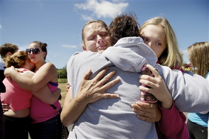Oregon School Shooting Brandi Wilson, left, and her daughter, Trisha Wilson, 15, right, embrace Trish Hall, a mother waiting for her student, as students arrived at the Fred Meyer grocery store parking lot in Wood Village, Ore., after a shooting at Reynolds High School Tuesday, June 10, 2014, in nearby Troutdale. A gunman killed a student at the high school east of Portland Tuesday and the shooter is also dead, police said. (AP Photo/Troy Wayrynen)