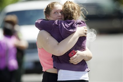 Oregon School Shooting Briannah Wilson, 21, left, and her sister Brittanie Wilson, 19, right, embrace after students arrived at shopping center parking lot in Wood Village, Ore., after a shooting at Reynolds High School Tuesday, June 10, 2014, in nearby Troutdale. A gunman killed a student at the high school east of Portland Tuesday and the shooter is also dead, police said. (AP Photo/Troy Wayrynen)