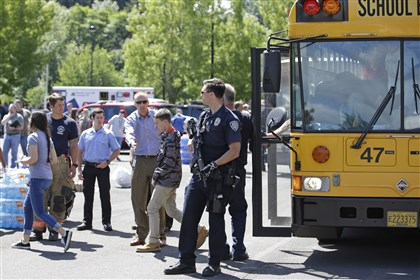 Oregon School Shooting A police officer stands guard as students arrived at a shopping center parking lot in Wood Village, Ore., after a shooting at Reynolds High School Tuesday, June 10, 2014, in nearby Troutdale. A gunman killed a student at the high school east of Portland Tuesday and the shooter is also dead, police said. (AP Photo/Rick Bowmer)