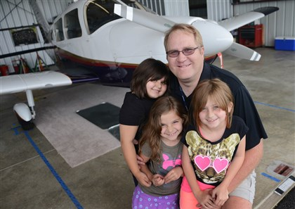 20140610MWHBeresnyakMag03-2 Frank Beresnyak with his three daughters -- Gabby (left), 6, and twins Bella and Anna, 7 -- at the Pittsburgh Flying Club's 1976 Piper Archer II at Arnold Palmer Regional Airport.