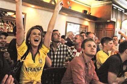 20140612CMLocalPipersPub001 Kelsey Hochleitner of South Side celebrates Brazil's first goal of the World Cup at Piper's Pub, a bar known for its gatherings of soccer fans.