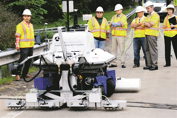 20140612ppFHARobot1LOCAL Federal Highway Administration officials, Rutgers Center for Advanced Infrastructure and Transportation researchers and Pennsylvania Department of Transportation officials watch a robot at work analyzing the condition of the bridge.