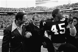 From the archives: In this Jan. 18, 1976, photo, Steelers coach Chuck Noll, center, leaves the field with Jim Allen (45) who holds up his finger indicating the Steelers are No. 1 after defeating the Dallas Cowboys 21-17 in Super Bowl X at the Orange Bowl in Miami.