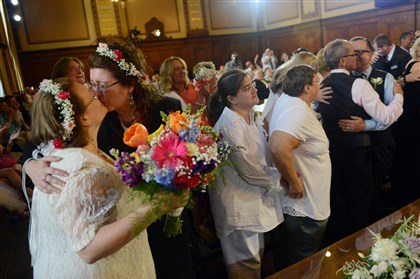 Same-sex wedding ceremony 06152014 Larisa Van Winkle, far left, 52, kisses her wife, Nancy Janda, 50, both of Penn Hills, as Pittsburgh Mayor Bill Peduto officiates a group same-sex wedding ceremony Sunday.