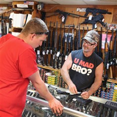 450717628 Danny Egan, right, helps a customer shop for a handgun Monday at Freddie Bear Sports in Tinley Park, Ill. In a 5-4 decision, the Supreme Court ruled that it is a crime for one person to buy a gun for another while lying to the dealer about who the gun is for.