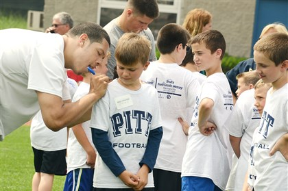 "Panther's DL Devin Cook Panther's DL Devin Cook, a sophomore, signs shirts of players at the ""Little Panther Camp"", held at the University of Pittsburgh Panther;s Pratice Facility on the South Side. The Little Panther Camp is for kindergarten and elementary school children."