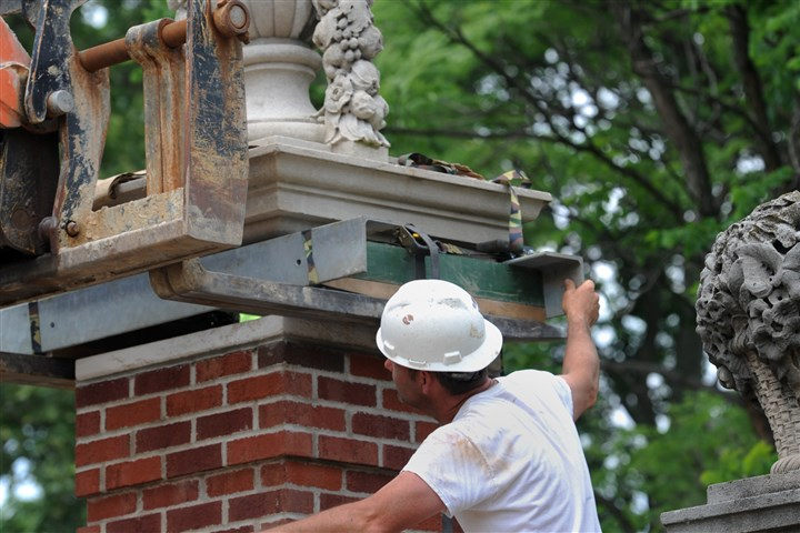 Scott Price of Marsa Inc. Scott Price of Marsa Inc., helps install carved stone capitals atop brick pillars that will flank a new wrought-iron entrance at The Frick Pittsburgh, Point Breeze. A new visitors center just inside the entrance opens to the public next month.