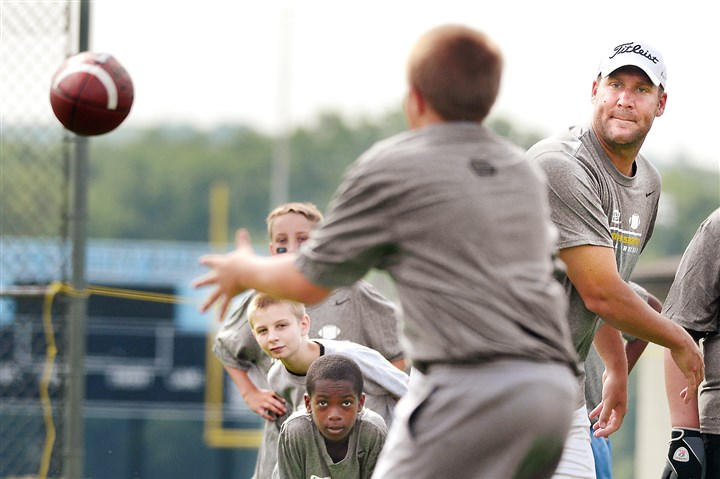 All eyes on the ball Steelers quarterback Ben Roethlisberger throws a pass Monday under the eyes of kids participating in the Ben Roethlisberger Football Procamp at Seneca Valley High School.