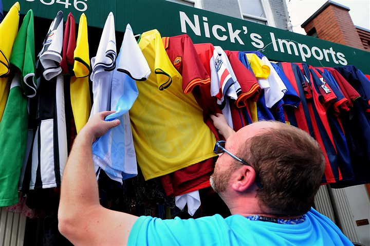 World Cup Sheridan Korey Bates of Sheridan shuffles through the line of soccer shirts available at Nick's Imports on the South Side.