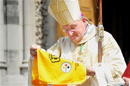 Bishop Zubik terrible towel Bishop David Zubik is presented with a Terrible Towel following the funeral of former Steelers head coach Chuck Noll at St. Paul Cathedral in Oakland.