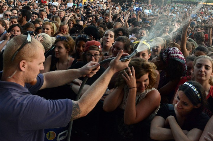 Arctic Monkeys4 06172014 David Dunn, of Landmark Events Staff, sprays water on the concert crowd at the Arctic Monkeys concert at Stage AE on the North Shore Tuesday.