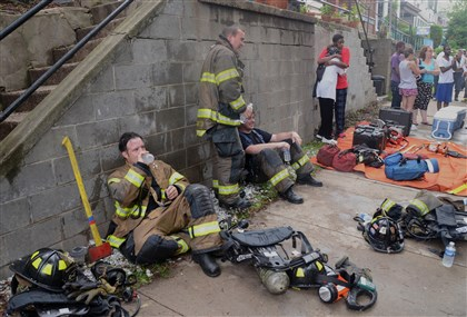 20140618ngFireLocal (2)-1 Pittsburgh firefighters take a water break after battling a fire in Garfield Wednesday morning.