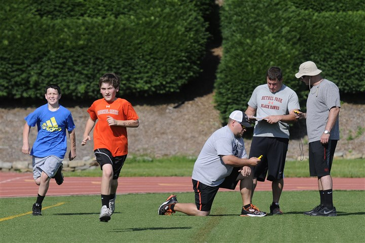 20140601jryouthfootballZone.jpg Tyler Thimons, 12, (left) and Matthew Casaldi, 12, jog back into line while coaches Dave Cole, Tony Dudowski and Rick DiRienzo record their 40-yard dash times during a combine for the Route 19 Youth Football League at Bethel Park High School earlier this month.