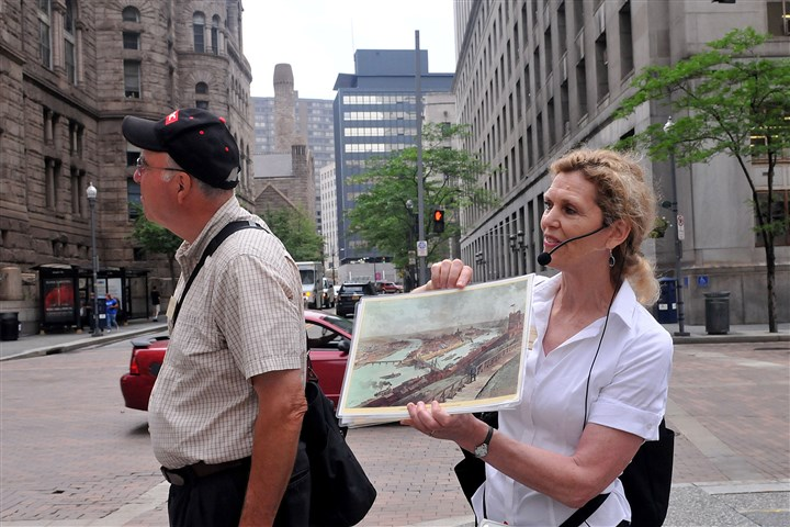 20140618lrtouristambassadors02-5 Louise Sturgess, director of Pittsburgh History & Landmarks Foundation, who gives downtown tours, stands at the corner of Forbes and Grant and describes the layout of the Golden Triangle while Tim Merrill, a docent with the foundation examines the Allegheny County Courthouse.