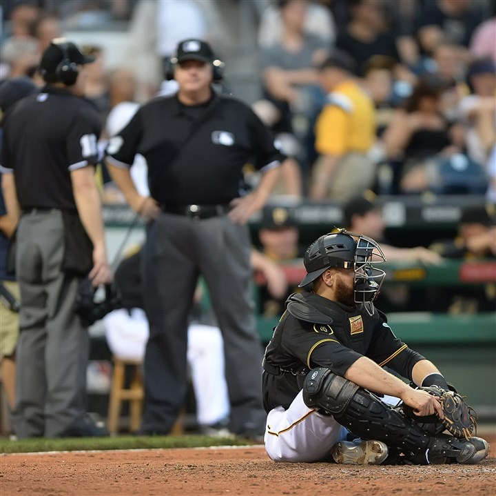 20140618pdPiratesSports04-1 Pirates catcher Russell Martin sits on home and waits for the umpires to look at the replay after Russell was called for blocking the plate.