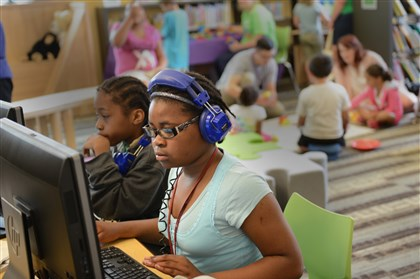 20140621ppHazelwoodLibrary1LOCAL-3 Evonna Chison, 11, of Hazelwood listens to music on the computer during the grand opening of the Carnegie Library of Pittsburgh at the Hazelwood Center.