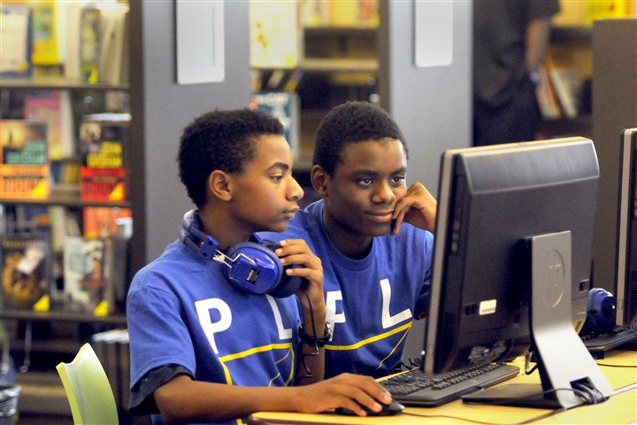 20140621ppHazelwoodLibrary2LOCAL-4 Davron Taylor-Gatewood, 13, and Njuan Fondren, 11, of Hazelwood try out the computers during the grand opening of the Carnegie Library of Pittsburgh at the Hazelwood Center.