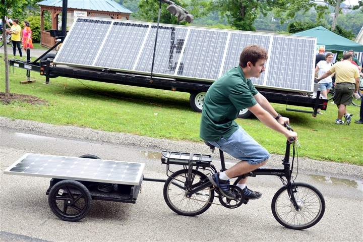 20140621lfSolarLocal01-11 Tim Polen, a PV-EV specialist of Adam Solar Rides, demonstrates a solar panel powered bike Saturday at the first Solar Festival in Millvale Riverfront Park.