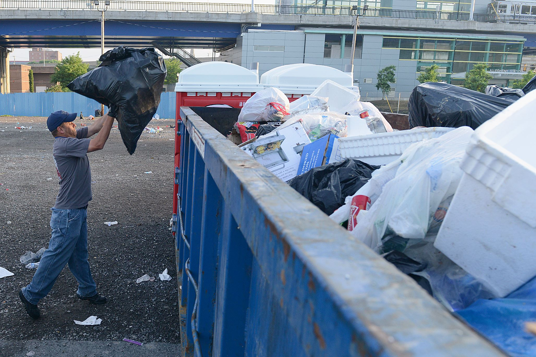Workers clean up trash from the Carnegie Science Center parking lot on the North Shore the morning after the June 21 Luke Bryan concert.