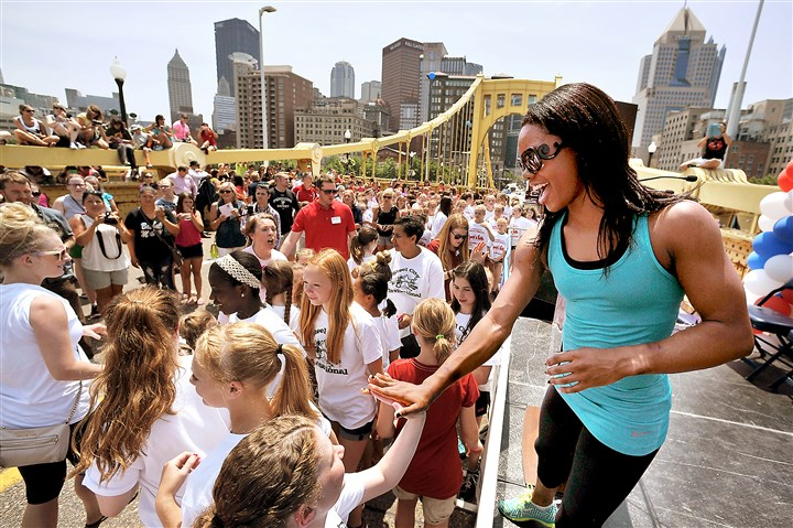 Gabby-Douglas-cartwheel-record Gabrielle Douglas, the 2012 Olympic all-around world champion, high-fives gymnasts on the Robert Clemente Bridge Monday afternoon. A total of 735 gymnasts filled the bridge in an attempt to break the world's record for most cartwheels done at one time. USA Gymnastics and CONSOL Energy Center hosted an Olympic Day on the span.