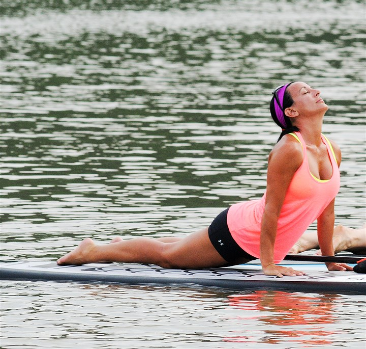 20140623CMPaddleYogaMag003-2 Lisa Volpe, owner of RiseUp, stretches on a paddle board during a RiseSUP yoga class on the Allegheny River near the Fox Chapel Yacht Club.