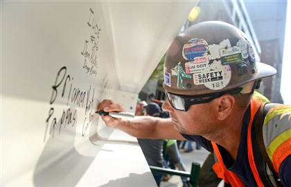 20140424MWHtoppingoffLocal01 Ironworker Kirk Galloway signs the final steel beam for the 33-story Tower at PNC Plaza during the topping off ceremony.