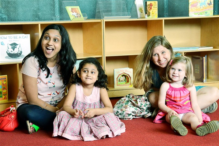 20140624lfReadingLocal01 Richa Buddineni, left, 30, of Squirrel Hill, and her 3-year-old daughter Arija, and Katharine Bulova, 42, of Point Breeze, and her 4-year-old daughter Vivienne, react to a story read by librarian Kristen Keller (not pictured) at the Carnegie Library Squirrel Hill branch on Tuesday.