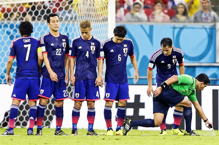 9q800rob Referee Enrique Osses from Chile puts vanishing spray on the pitch to mark where the Japan wall should be for a free kick during a Group C World Cup soccer match against Ivory Coast.