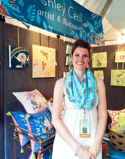 20140629Style1 Artist and illustrator Ashley Cecil wears one of the infinity scarves featuring patterns adapted from her paintings in her booth at the Dollar Bank Three Rivers Arts Festival earlier this month. She's surrounded by her paintings and pillows, which also include patterns inspired by her art.