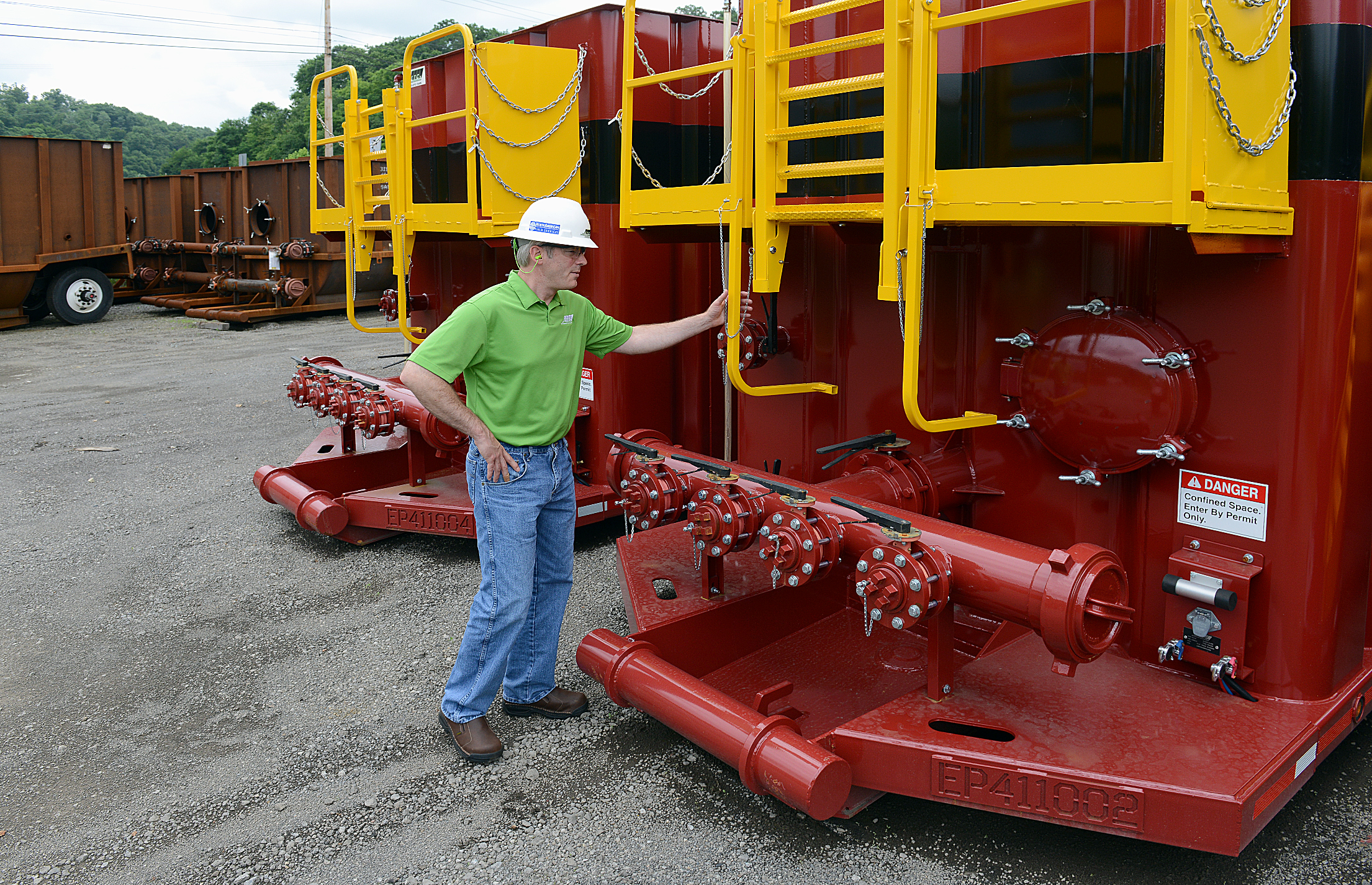 20140625radETCJohnstownBiz06-5 Matt Hughes stands with finished frack tanks at ETC's Johnstown office. The company is one of two in the Marcellus Shale that manufactures such tanks.