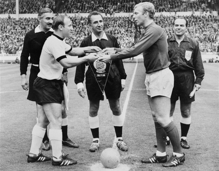 captains of the German and English national soccer teams The captains of the German and English national soccer teams, Uwe Seeler, left, and Bobby Moore exchange pennants at Wembley stadium in London before the start of the World Cup final between the two countries on 30 July 1996. Swiss referee Gottfried Dienst is at center.
