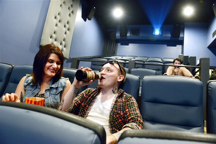 "20140627bwTheaterZones02-1 Roxana Gilani of Lawrenceville and Travis Ayers of Hampton Township watch trailers before a showing of ""The Shinning"" at Row House Cinema in Lawrenceville."