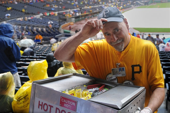 "20140706rldHotDog09-8 Rain doesn't detour hot dog vendor David Sakulsky, nicknamed ""Chico,"" during a rain delay of the Pirates game against the Cincinnati Reds at PNC Park on June 19. Even with the rain, he quickly sold out his last batch of 20 hot dogs."