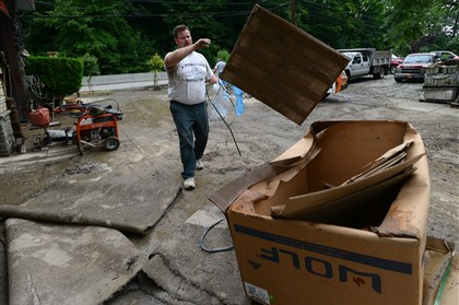 ScottFloodLocal02-1 Bill Carnes adds to the trash pile as workers clean up at A. Petrelli & Sons Contracting on Hope Hollow Rd. in Scott Sunday morning following Saturday night's flooding from storm water runoff. It's the second time in the past two years the business has been flooded.