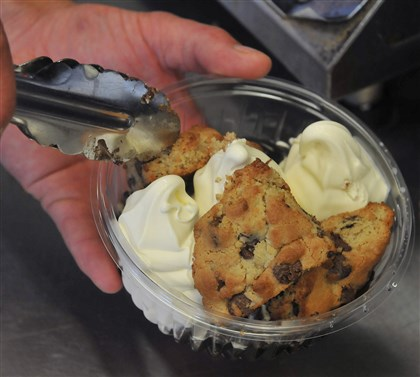 20140629lricecreamfood04-3 Alexander Page puts Nancy B's chocolate chip cookies on top of vanilla soft-serve ice cream for a Hot Chocolate Chip Cookies Sundae at Page's Dairy Mart.