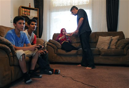 The Koc family Yunus, far left, and Muhammed play a video game while Bunyamin Koc shows something to his daughter, Zeynep, while she relaxes on a couch at home.