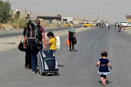 Iraq 0630 An Iraqi family leaves their hometown Mosul, walking toward Irbil, on the outskirts of the northern city of Mosul, Iraq. The al-Qaida breakaway group that has seized much of Syria and Iraq has formally declared the establishment of a new Islamic state, demanding allegiance from Muslims worldwide.