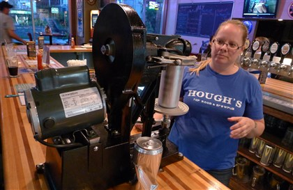 20140701bbHoughFood Bridget Smidga, manager at Hough's in Greenfield, seals a Crowler on the new machine on the bar. A Crowler is the trademarked name for a 32-ounce can that also is a growler -- a container that the bar fills with draft beer for customers to take home.