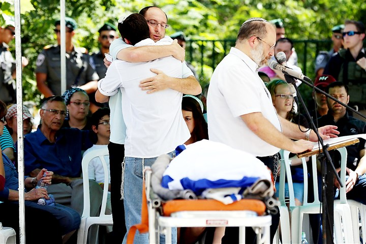 9qp00m04-17 Ofir, the father of Gilad Shaer, 16, hugs a mourner as they stand in front of his son's body during a funeral service at his hometown, the Talmon Jewish settlement, near the West Bank city of Ramallah, on Tuesday.