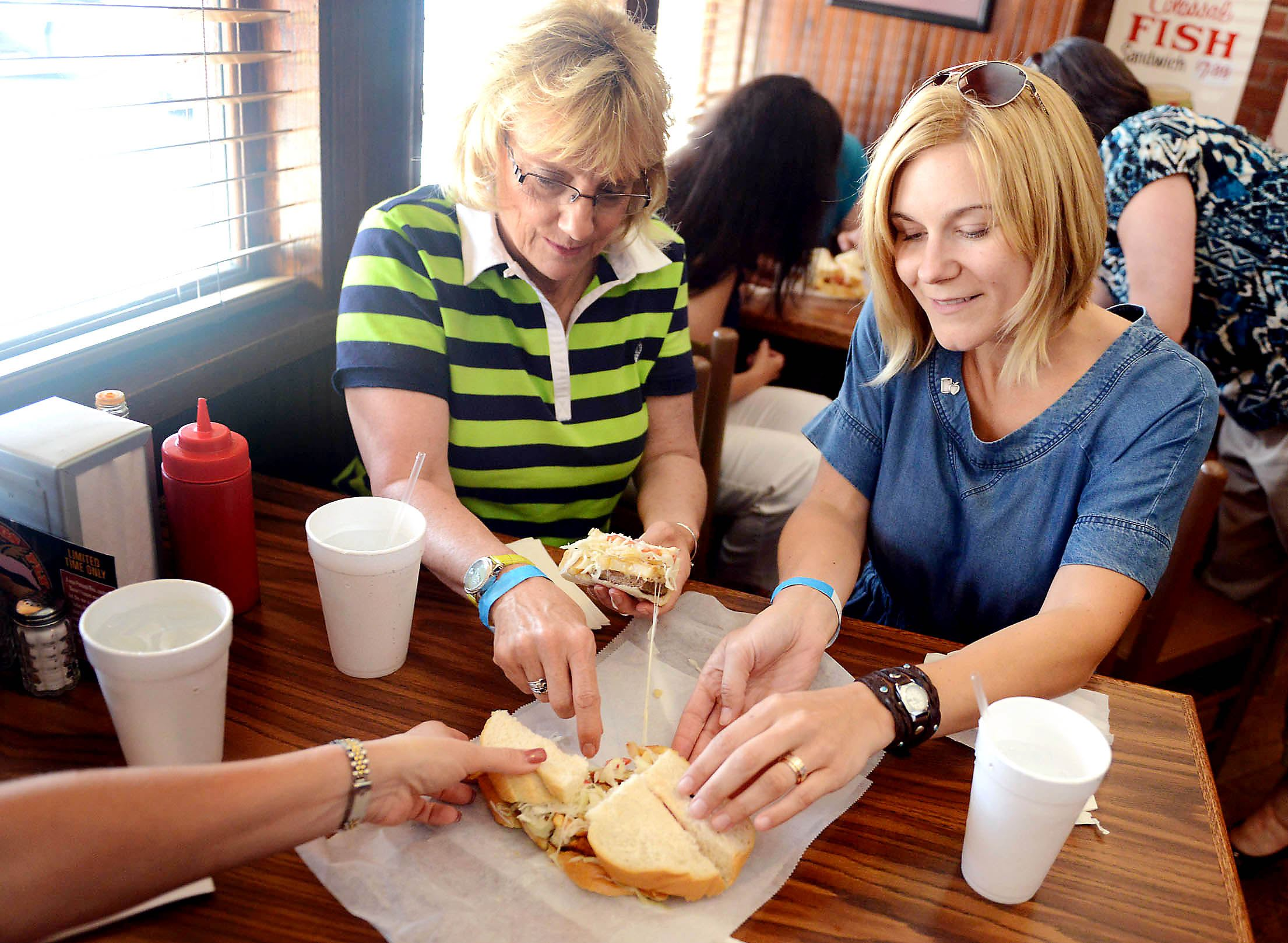 20140627MWHfoodtourFood02-1 Jacqueline Spirnak, left, of Bridgeville, and Alyssa Jurewicz-Johns, of Shadyside, pick up fourths of a Primanti Brothers sandwich at their Strip District location during the Flavor of Pittsburgh Food Tour on June 27, 2014.